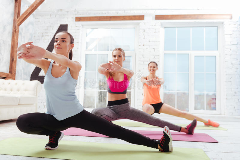 Three delighted women doing fitness exercises together stock images