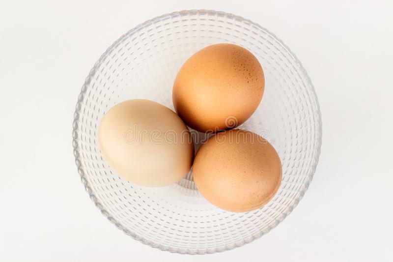 Three different color eggs in bowl stock photography