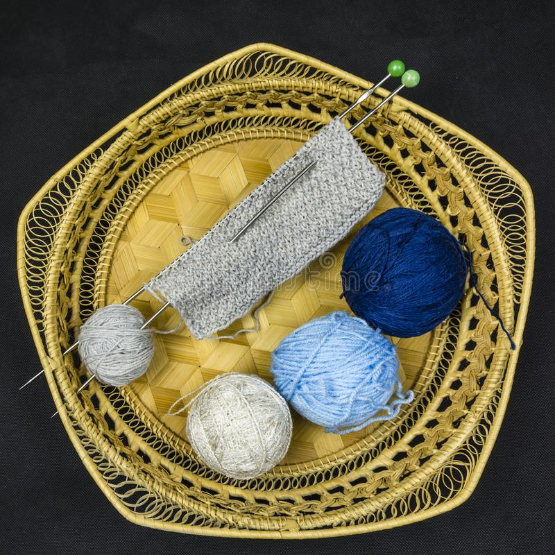 Three different colored balls of wool and the start of knitwork. Three different colored balls of wool and the start of the manual knitting on the wires placed stock photography