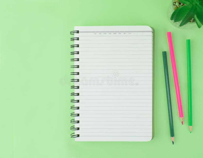 Three different colored pencil crayons scattered beside a notebook and a miniature plant on a green background royalty free stock image