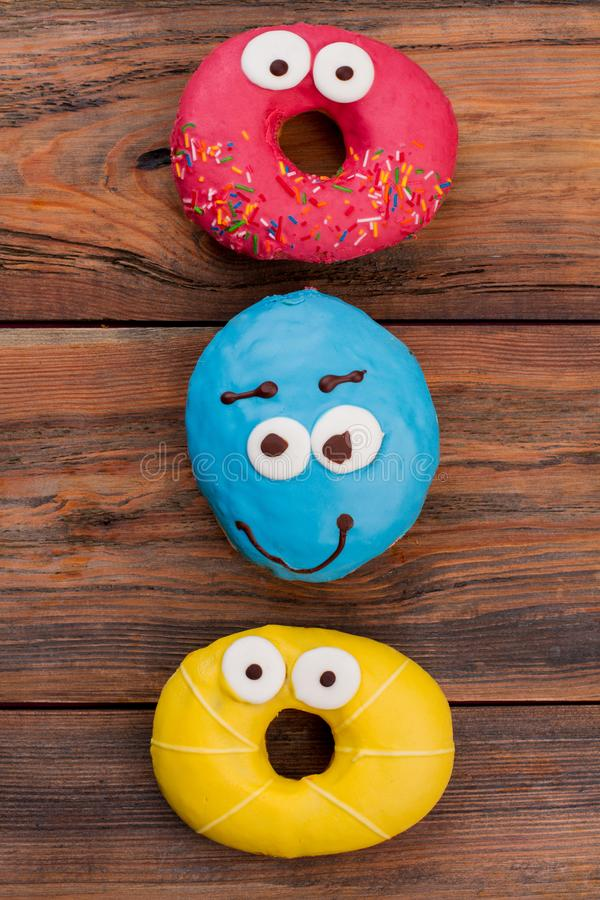 Three different donuts with surprised eyes. royalty free stock photos