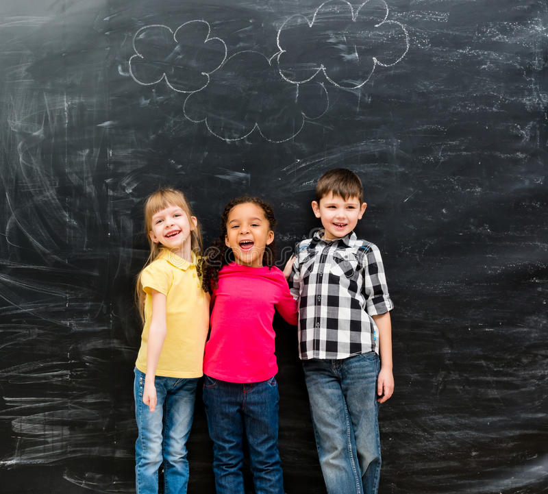 Three different laughing children with blackboard on background stock photo