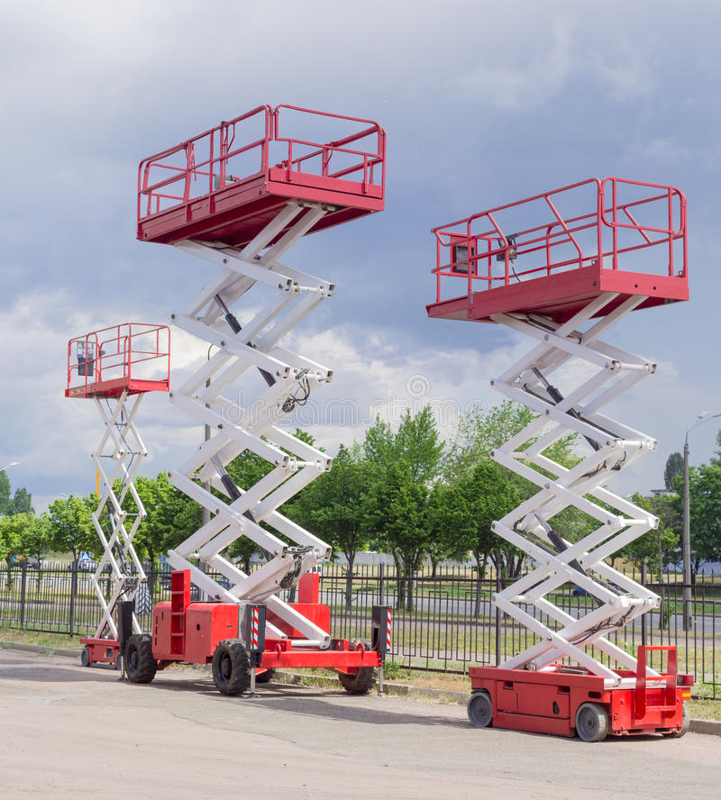 Three different scissor wheeled lifts on asphalt ground. Three different red and white scissor wheeled lifts on an asphalt ground on the background of sky with stock photography