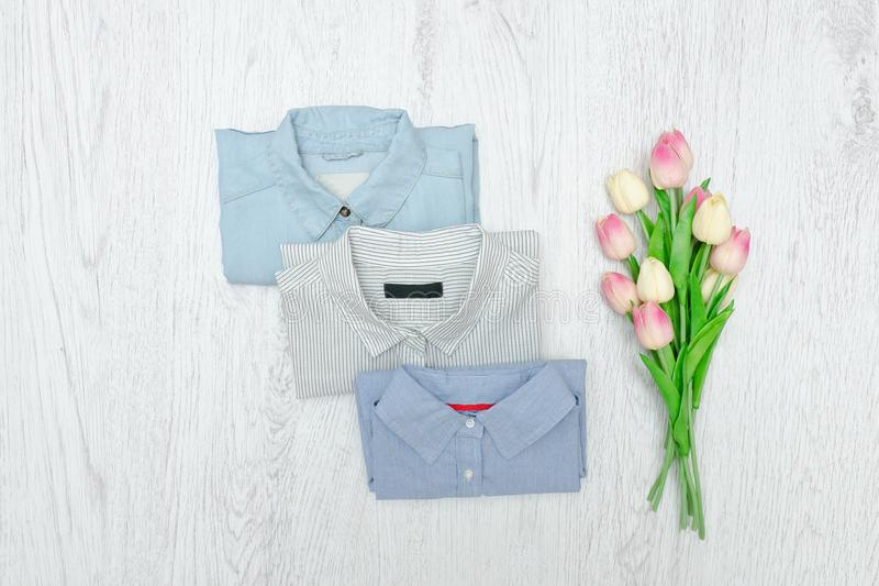 Three different shirts and a bouquet of tulips. Fashionable concept. Assortment.  royalty free stock images