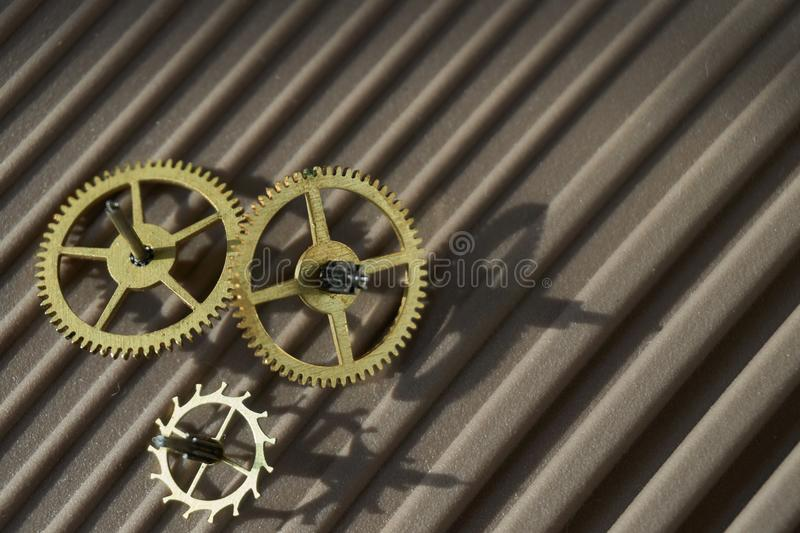 Three different toothed brass metal cog wheels stock image