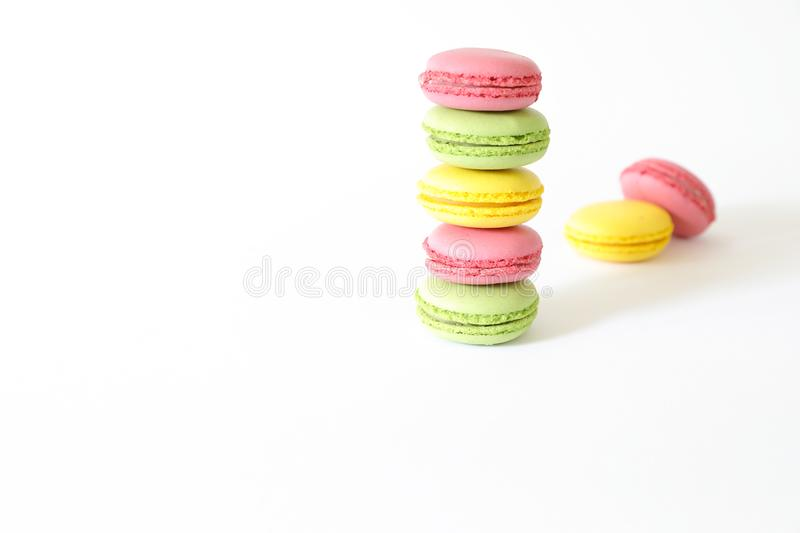 Three different types of macaroons colors pink, green and yellow isolated on white background. royalty free stock photo