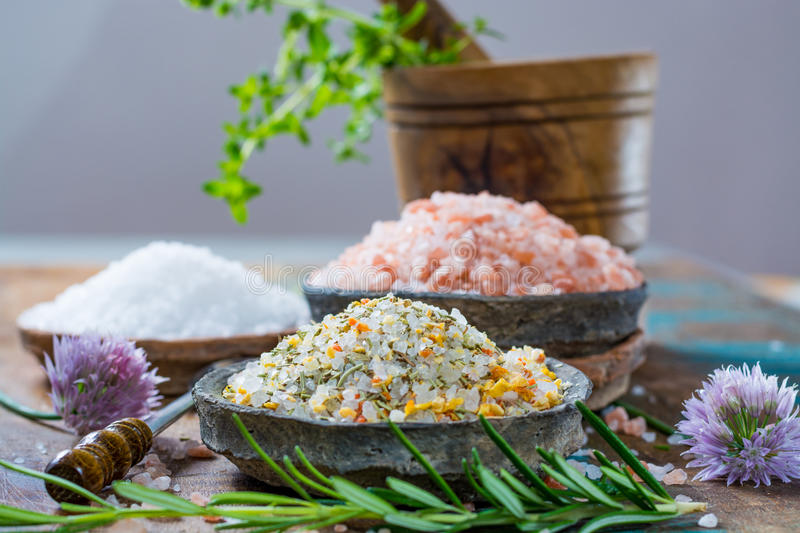 Three different types of natural salt in stone bowls on wooden s. Different types of natural salt in stone bowls on wooden surface. White sea salt, pink royalty free stock photo