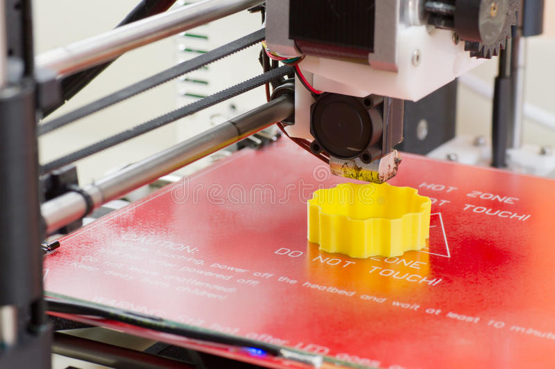 Three dimensional printer in action. Detail of a 3D printer printing with a yellow ABS filament royalty free stock photos