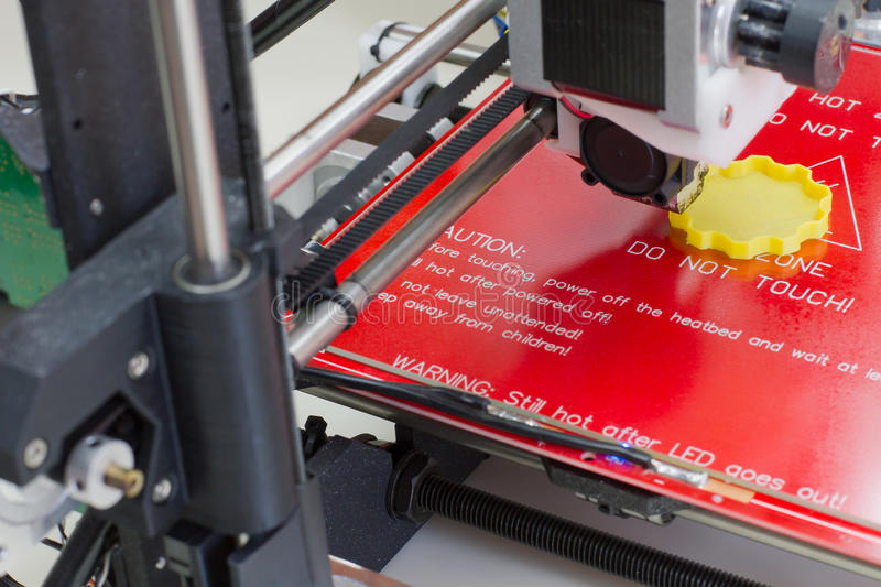 Three dimensional printer in action. Detail of a 3D printer printing with a yellow ABS filament royalty free stock images