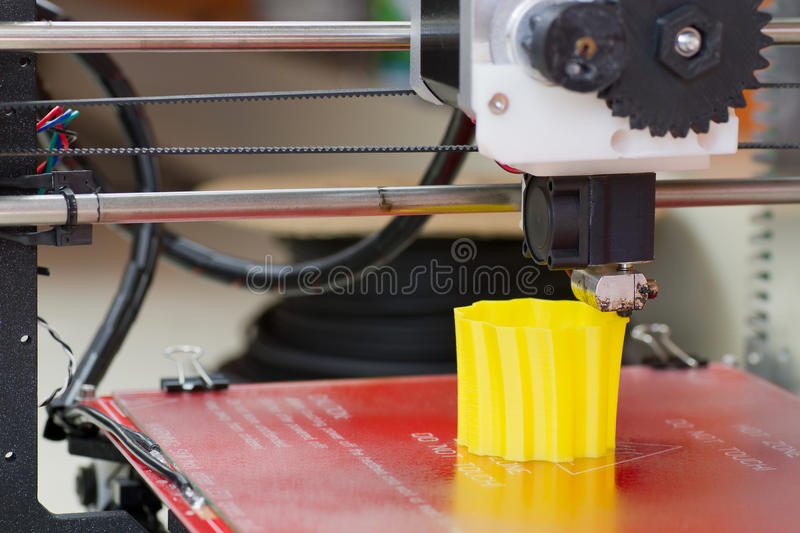Three dimensional printer. Detail of a 3D printer with a yellow plastic filament royalty free stock photo