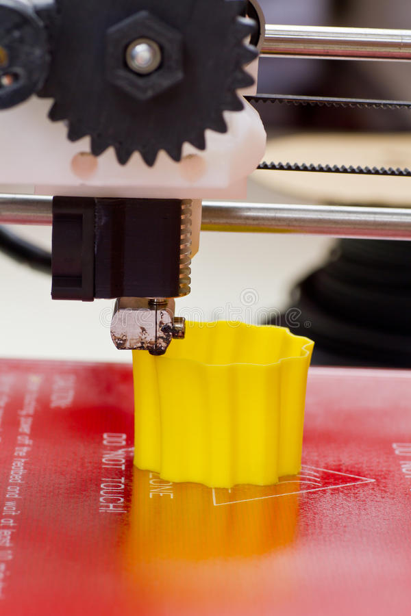 Three dimensional printer. Detail of a 3D printer with a yellow plastic filament stock photos