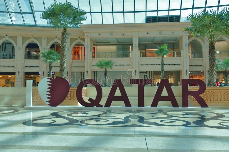 Three-dimensional writing `I love qatar` in one of the many shopping centers in Doha, Qatar. Three-dimensional writing at a man`s size `I love qatar` in one of stock image