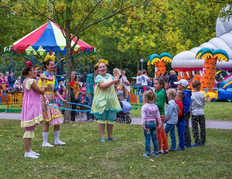 Three disguised women and a group of children playing in the fresh air stock photography