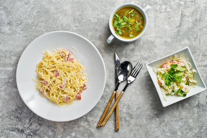 Three dishes in the restaurant, Pasta Carbonara, green salad and chicken soup. royalty free stock photography