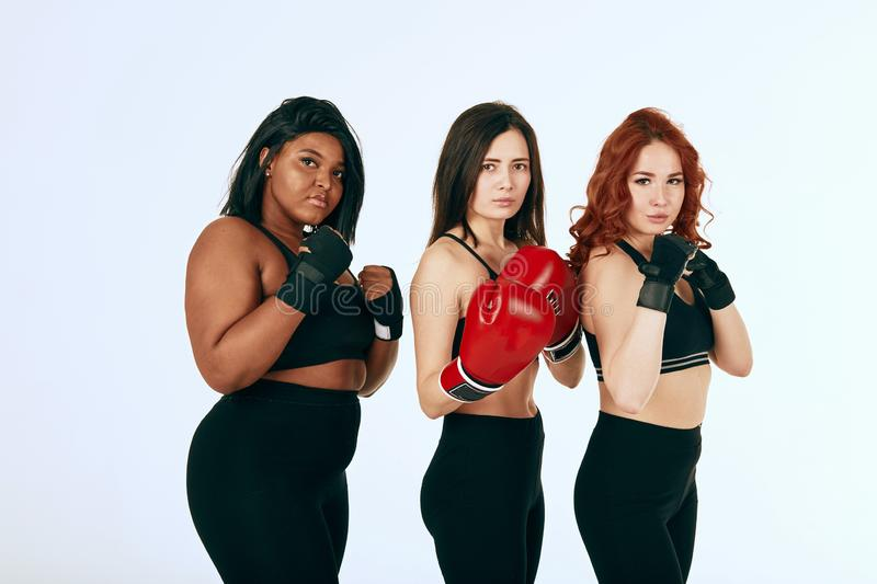 Three multiracial diverse woman in black sportswear posing in boxing gloves royalty free stock images