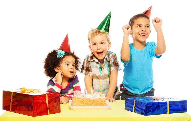 Birthday cake. Three diversity looking kids on birthday party with presents and cake, very exited, laughing and smiling, isolated on white royalty free stock photography
