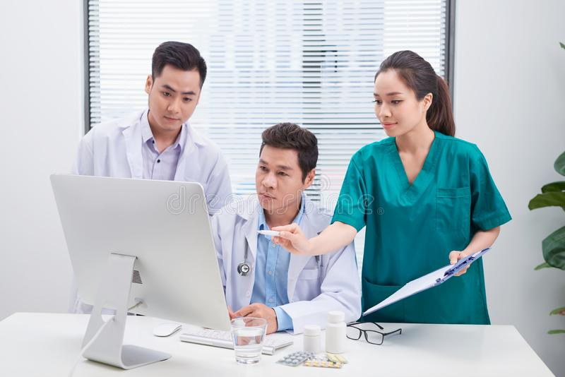 Three doctors discussing patient files on office royalty free stock photography