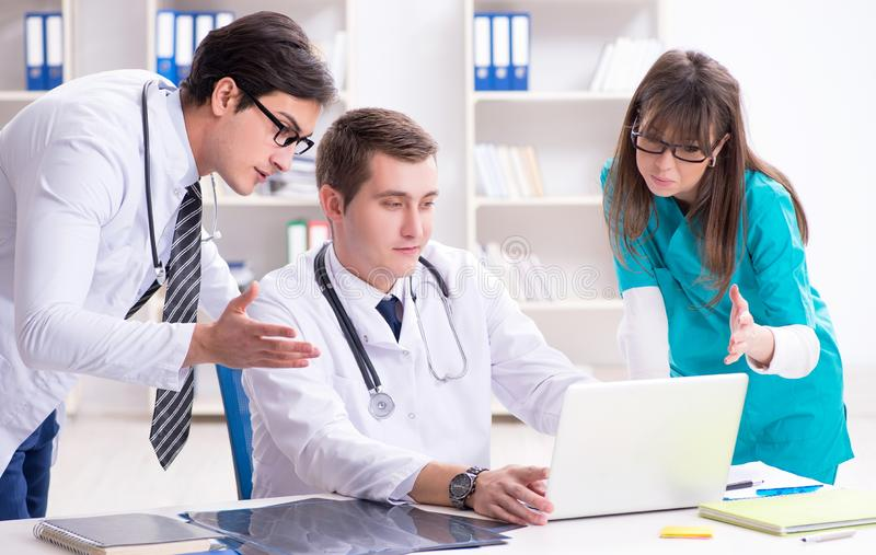 The three doctors discussing scan results of x-ray image stock photography