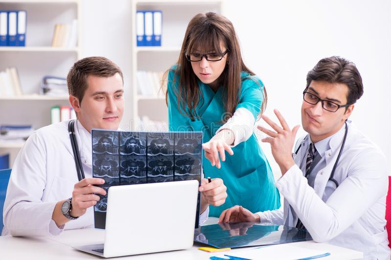 The three doctors discussing scan results of x-ray image royalty free stock image