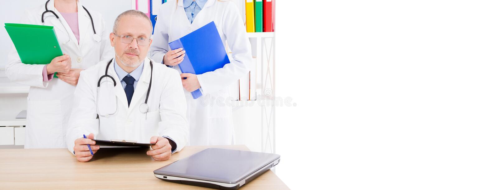 Three doctors posing in the clinik medical office,copy space,billboard or banner royalty free stock images