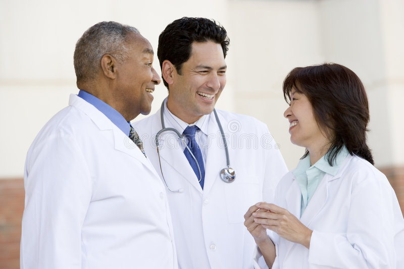 Three Doctors Standing Outside A Hospital. Talking stock photography