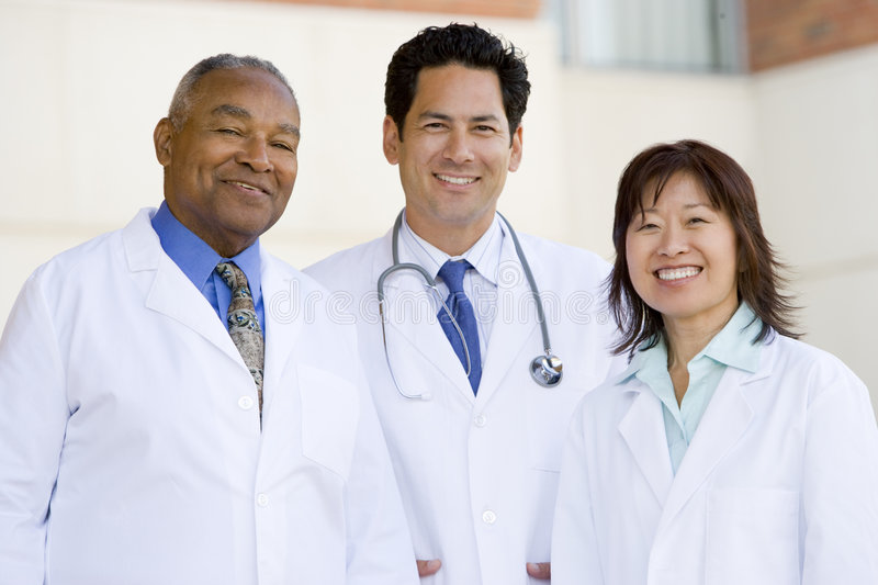 Three Doctors Standing Outside A Hospital. Smiling stock image