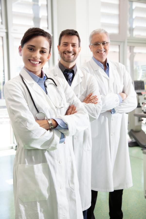 Three doctors. Team of smiling doctors in white coats royalty free stock images