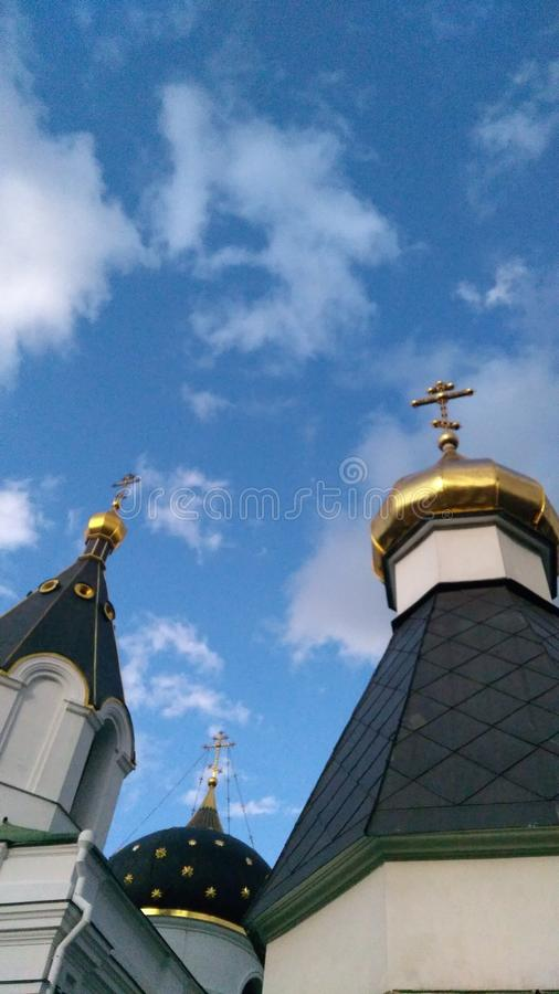 Three domes with golden crosses of the Russian Orthodox Church under blue sky with clouds royalty free stock photo