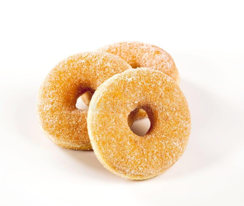 Three donuts. Studio shot of three fresh sugared donuts royalty free stock image