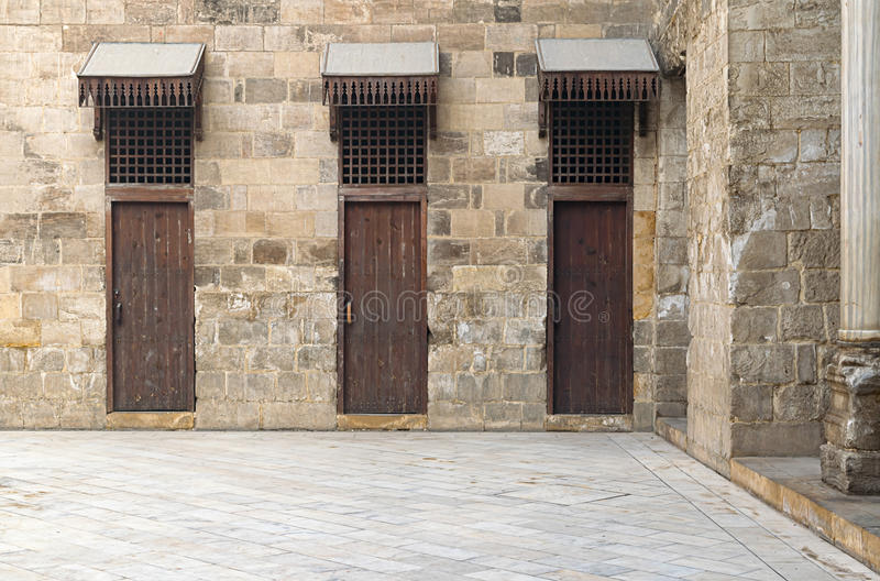 Three doors in a stone wall at the main courtyard in a historic stock photography