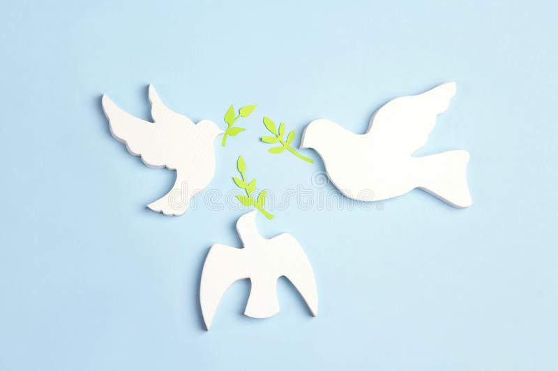 Three doves of  peace with olive branches on a blue background stock images
