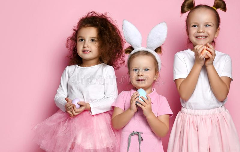 Three dressed up for the holiday kid girls with painted eggs are waiting for a miracle on Easter day stock photos