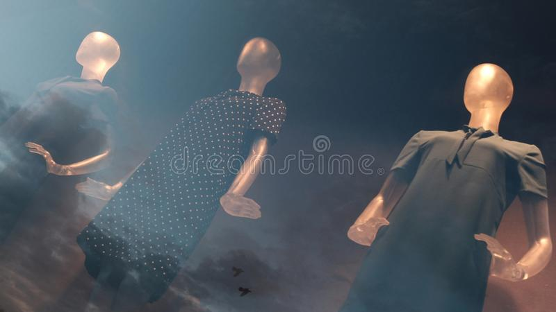 Three dummies on a storefront with a reflection of the evening sky. Double exposure effect. Background for topics about sales, dis stock photography