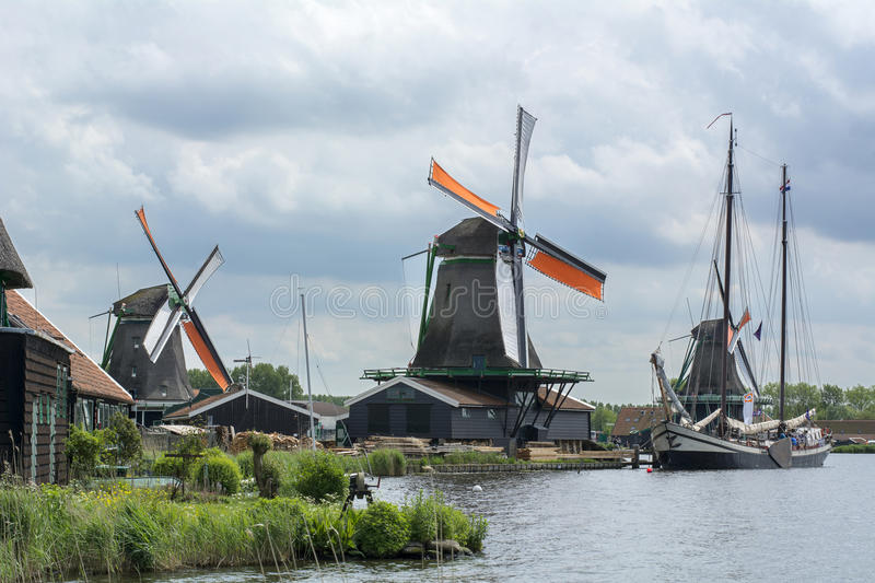 Three dutch mills with orange wings near the canal with one beautiful boat under the cloudy sky. In Zaanse Schans Netherlands stock photography