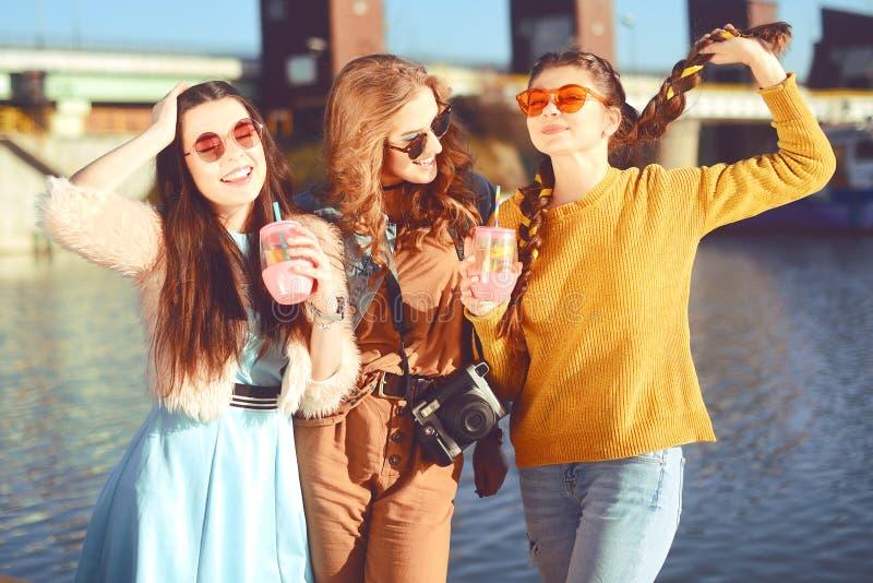 =Three dziewczyny blisko rzeki przeciw niebu ma zabawę Mod dziewczyny w okularach przeciwsłonecznych Skok, raduje się, pije, napo obraz stock