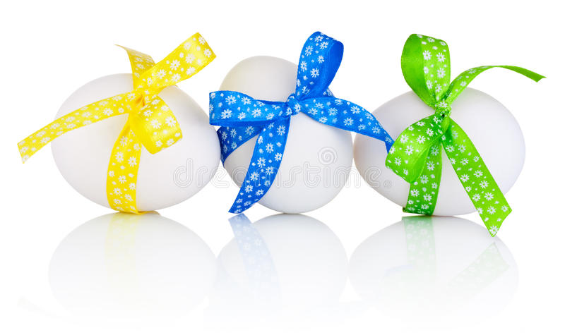 Three Easter eggs with festive bow isolated on white background stock photo