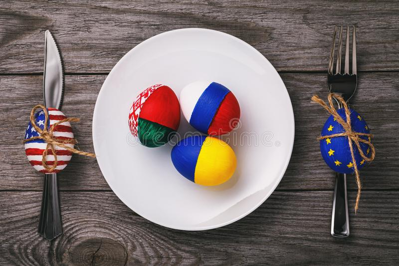Three easter eggs painted in the color of the flags of Russia, Ukraine and Belarus in a white plate on a wooden table stock image