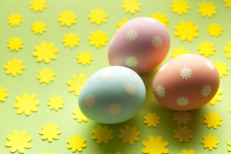 Three Easter eggs in pastel color on green background royalty free stock image