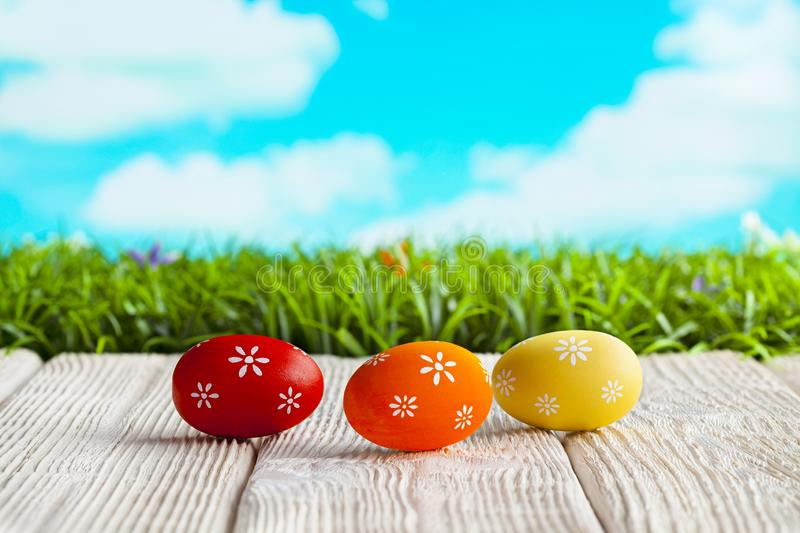 Three Easter eggs on white table and nature background stock image