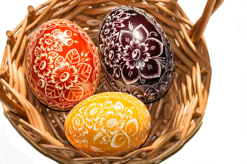 Three Easter eggs in woven basket stock photography