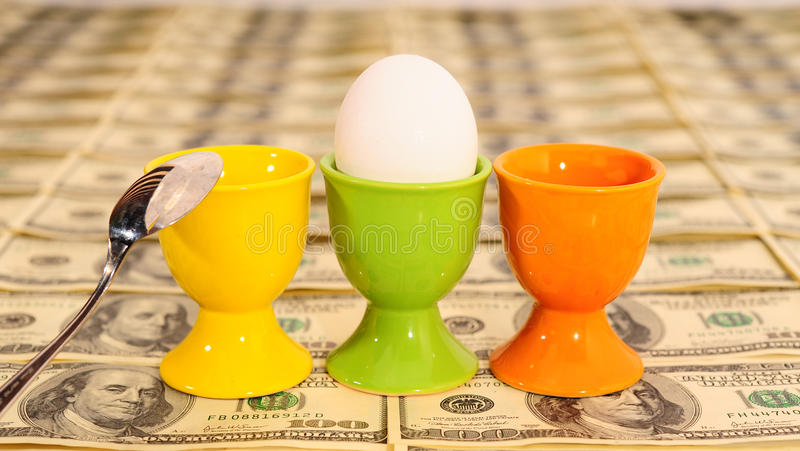 Three Eggs. In Eggcups On Background With Many American Hundred Dollar Bills stock images