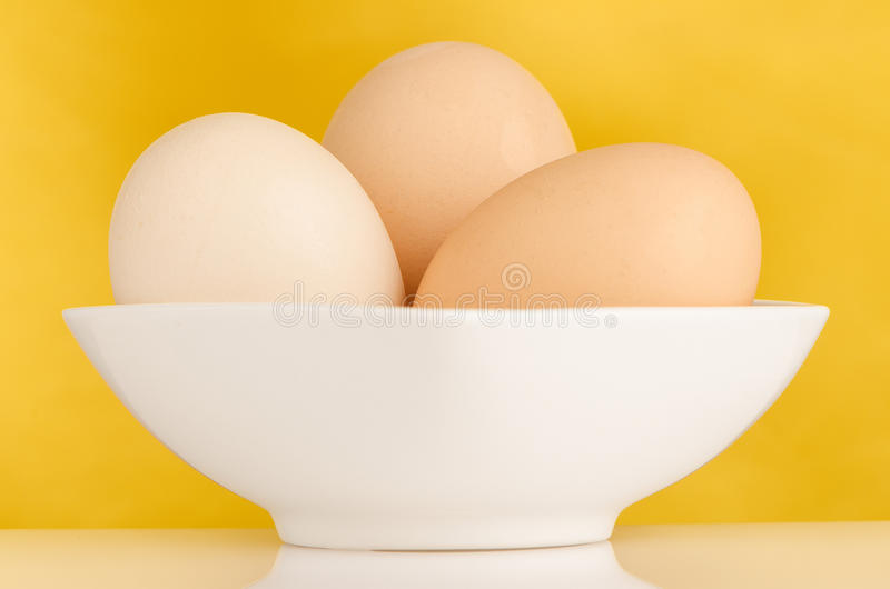 Three eggs in the bowl stock photos