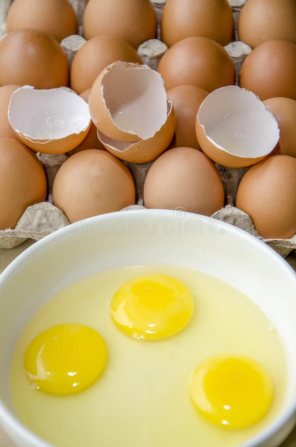 Three eggs in a bowl with their yellow yolks stock images