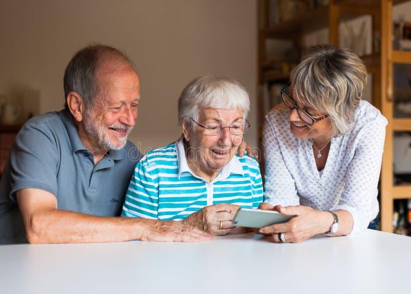Three elderly persons using smart phone stock photography