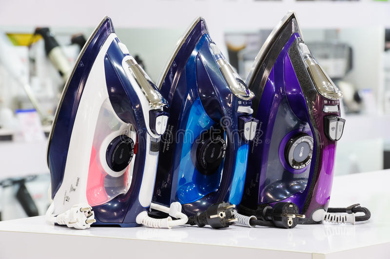 Three electric irons in retail store. Three colored electric irons at retail store shelf, defocused background royalty free stock image