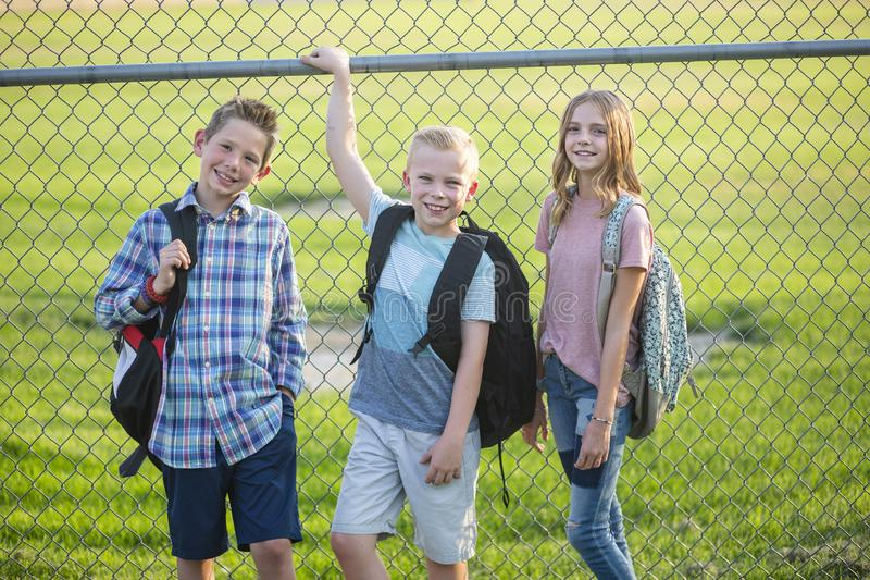 Three Elementary school students standing by a fence outside of their school stock photography