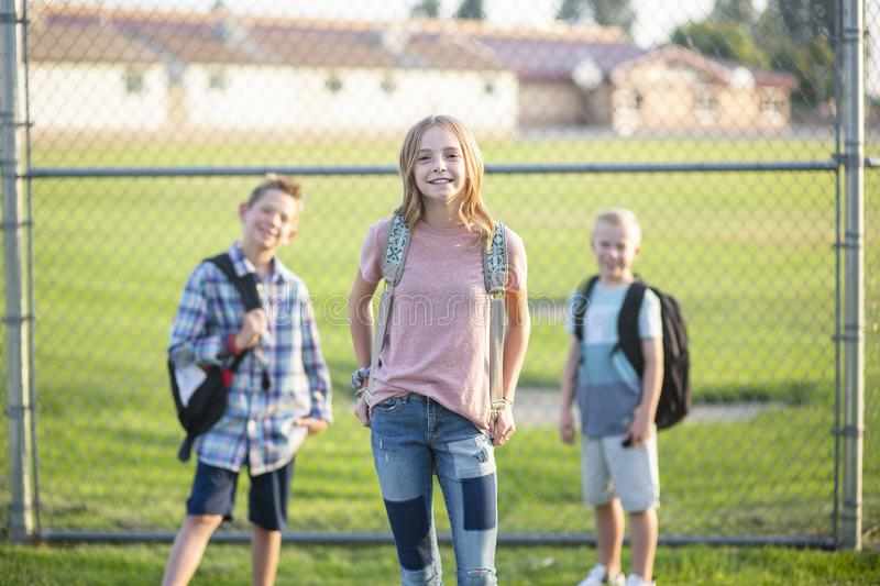 Three Elementary school students standing by a fence outside of their school. Yard. Smiling and ready to go to school. Selective focus on the girl student in royalty free stock photo