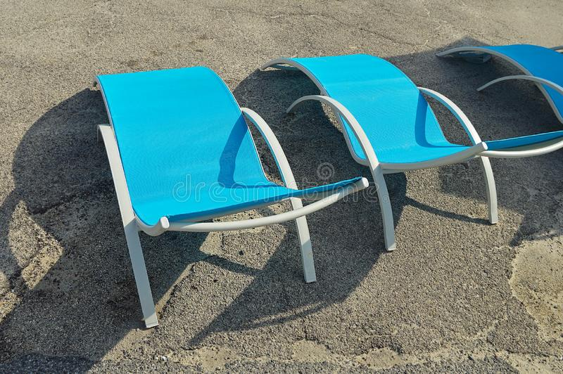 Three empty beach chairs. Made of metal and plastic on the asphalt pavilion stock photo
