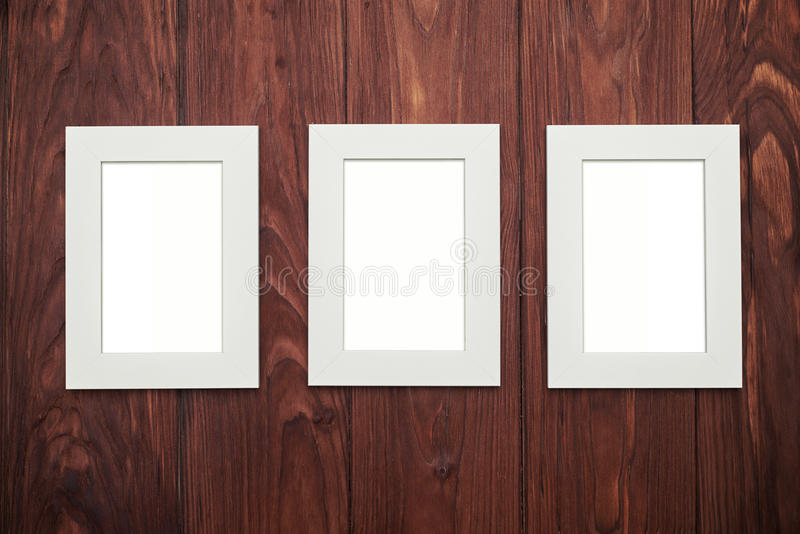 Download Three Empty Frames In The Middle On Brown Wooden Desk Stock Illustration - Illustration: 70384674