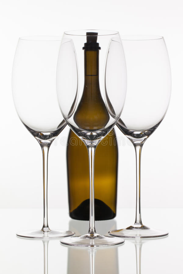 Three empty glasses of wine and brown bottle. On the white background royalty free stock photography